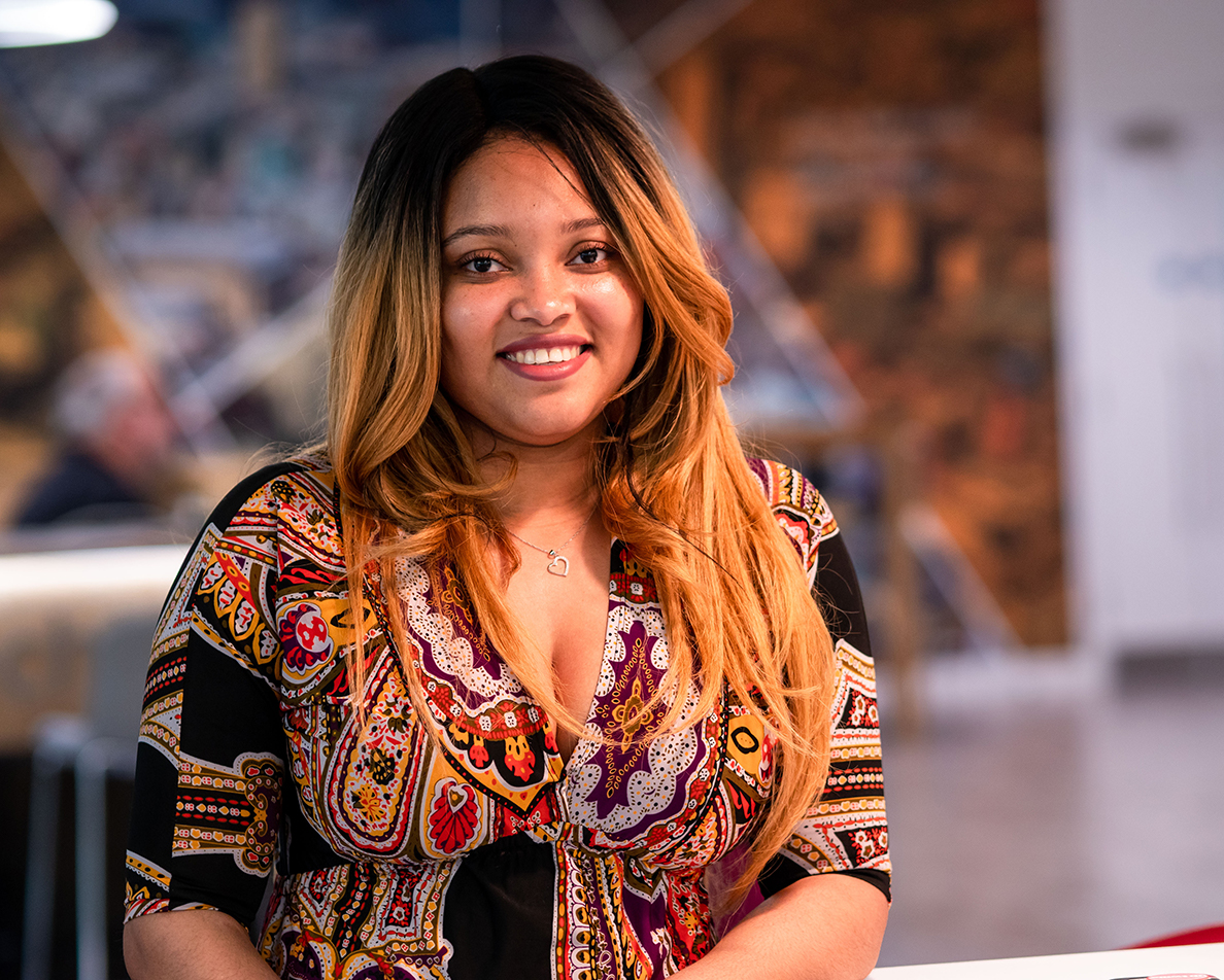 Fey Ijaware, front-end developer at DWP Digital, standing and smiling at the camera
