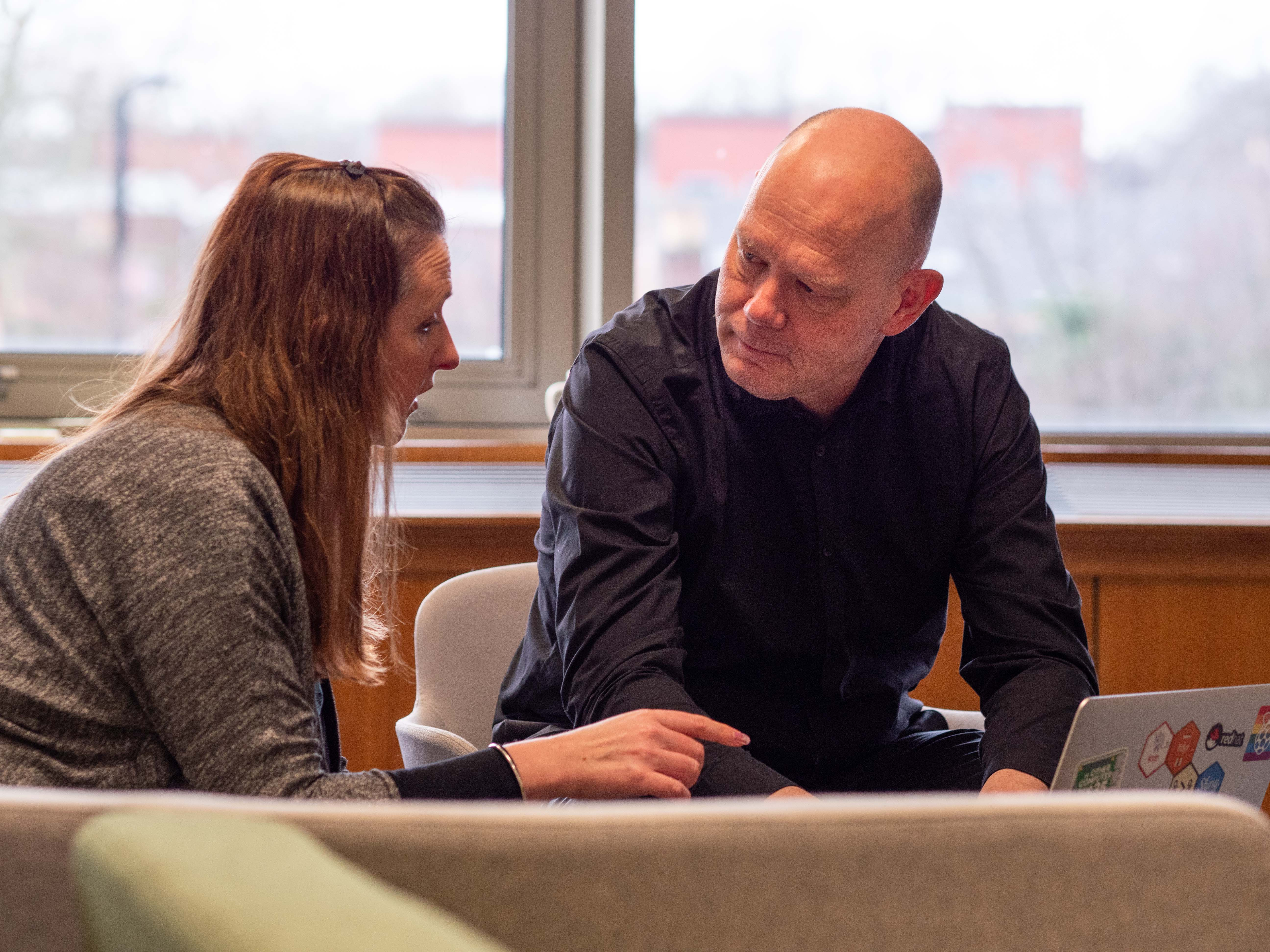 Pieter, wearing a black shirt, sitting in an informal meeting area, talking to a female colleague