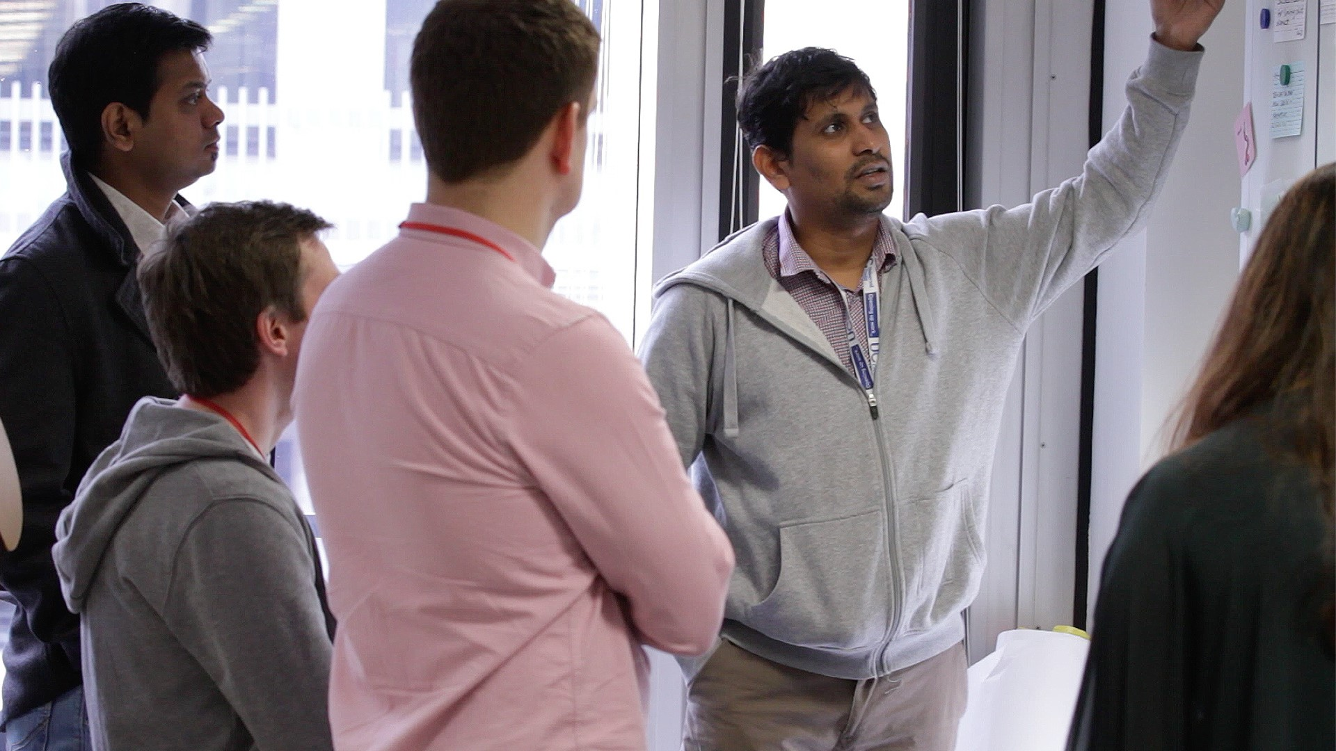 Image of group of colleagues looking at a whiteboard