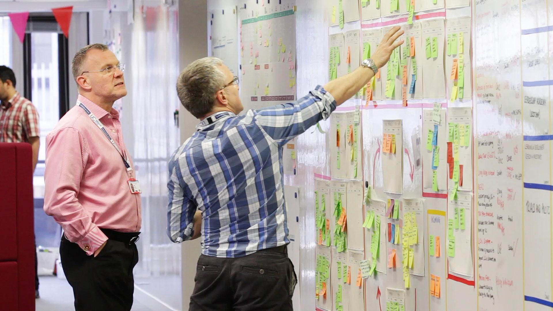 Image of two men looking at post-its on a whiteboard