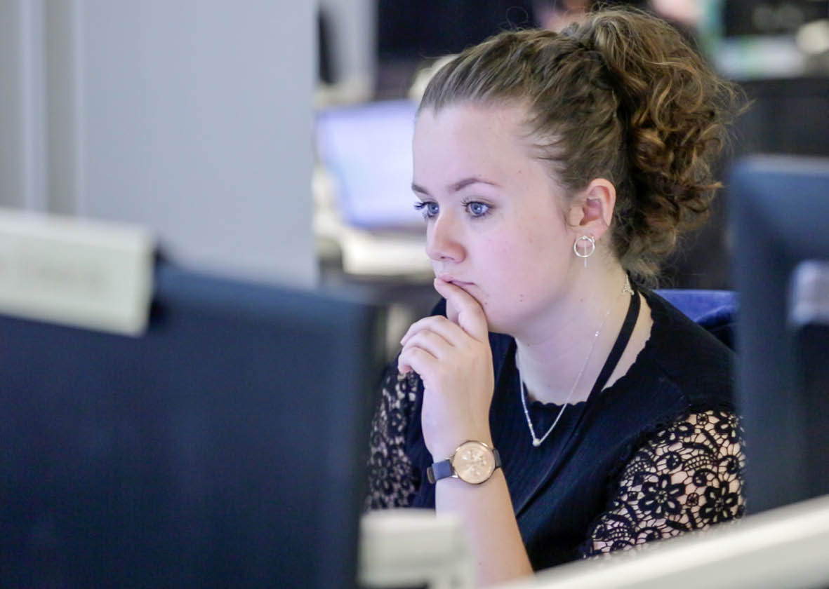 Woman looking thoughtfully at a computer monitor
