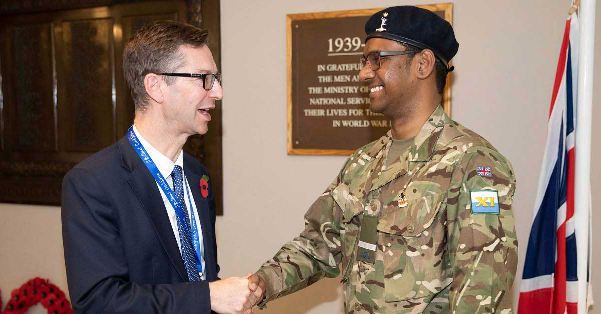 Nava in his Royal Corps uniform shaking hands with Peter Schofield DWP Permanent Secretary