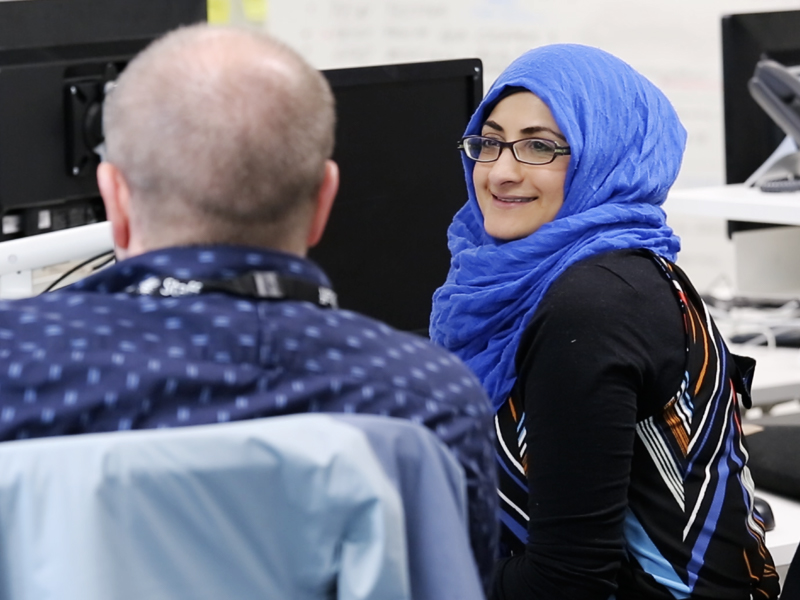 A woman wearing a hijab smiling and talking to a colleague. They are seated in front of computer screens.